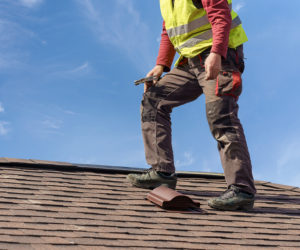Unrecognizable workman standing on tile roof of new home under construction against blue sky with helmet in hands