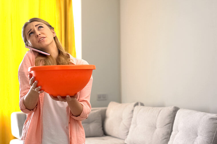 Woman catching roof leak with bowl