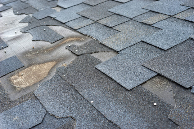 lose up view of bitumen shingles roof damage that needs repair.